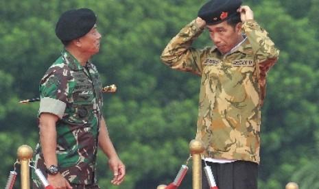 Presiden Jokowi memakai baret Mabes TNI disaksikan Panglima TNI Jenderal Moeldoko di Mabes TNI, Cilangkap, Rabu (16/4).