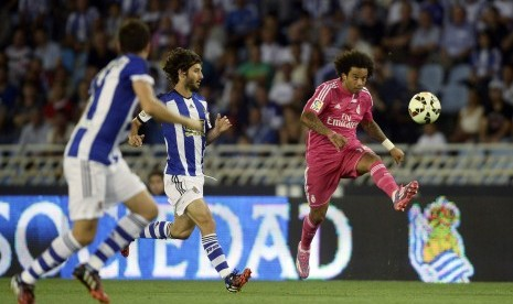 Real Madrid's Marcelo (R) kicks the ball during their Spanish first division soccer match against Real Sociedad at Anoeta stadium in San Sebastian August 31, 2014.