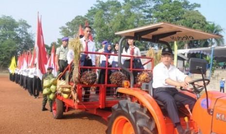Rektor IPB Prof. Dr. Ir. Herry Suhardiyanto, M.Sc mengemudikan traktor yang membawa perwakilan mahasiswa baru dari berbagai jenjang.