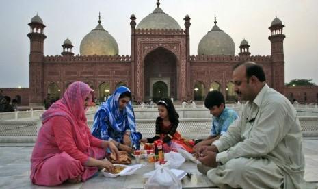 Sebuah keluarga Pakistan tengah menanti saat berbuka puasa di Masjid Badshahi di Lahore, Pakistan, Sabtu 21/7). (K.M. Chaudary/AP)