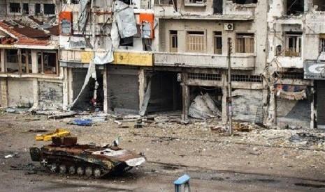 Sebuah tank yang hancur terlihat teronggok di jalanan wilayah al-Qossur propinsi Homs, Suriah , Senin (13/5).