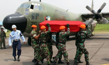 Sejumlah anggota TNI AU mengangkat peti yang berisikan jenasah dari korban pesawat pesawat Hercules C-130 saat proses pengembalian jenazah korban di Lanud Soewondo Medan, Sumatera Utara, Rabu (1/7).