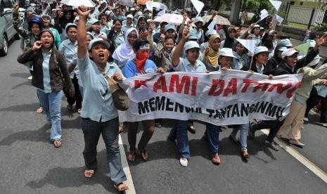Sejumlah buruh membentangkan spanduk ketika berunjuk rasa menuntut revisi dan penyesuaian upah minimum kabupaten/kota (UMK).