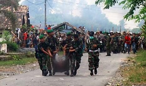 Sejumlah petugas TNI mengevakuasi korban bentrok antar warga di lokasi kejadian Desa Sidoreno Kecamatan Waypanji, Lampung Selatan, Ahad (28/10).