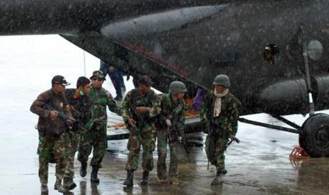 Sejumlah prajurit TNI memapah rekan mereka yang menjadi korban penembakan dan penyergapan kelompok sipil bersenjata setibanya di Bandara Sentani, Kabupaten Jayapura, Papua, Ahad (24/2).