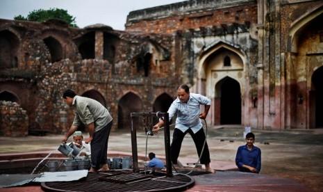 Sejumlah pria menimba air dari sumur untuk kebutuhan wudhu jamaah sebelum shalat Jumat pertama Ramadhan di masjid peninggalan era Mughal, New Delhi, India,