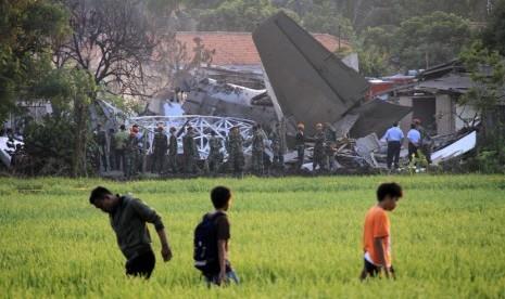 Sejumlah warga menyaksikan bangkai pesawat Fokker 27 yang jatuh di komplek Rajawali, Lapangan Udara Halim Perdana Kusuma, Jakarta, Kamis (21/6).  (Adhi Wicaksono/Republika)