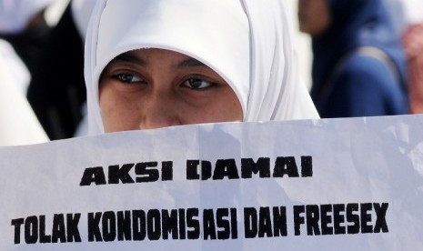 Seorang aktivis berunjuk rasa menolak sosialisasi kondom. Mereka mengecam kebijakan pemerintah yang menggelar kampanye kondom bagi remaja karena dianggap melegalkan perzinaan.