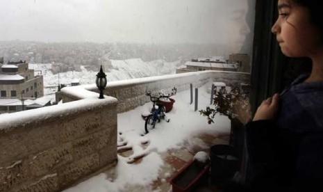 Seorang anak menyaksikan hujan salju dari jendela kamar tidurnya, di Amman, Yordania, Kamis (10/1).