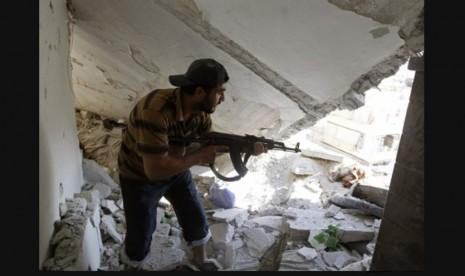 Seorang anggota Tentara Pembebasan Suriah berjalan di puing reruntuhan apartemen yang diserang peluru tank militer ketika bentrok terjadi di Aleppo (/Reuters/Goran Tomasevic)