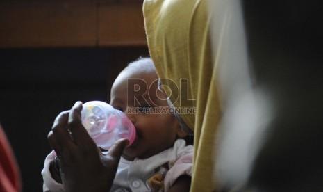 Seorang ibu memberi air minum anaknya yang berusia 4 bulan saat mengungsi di Gedung LBH Jakarta, Selasa (9/7). (Republika/ Tahta Aidilla)