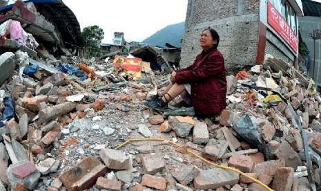 Seorang ibu merapat dan menangis setelah gempa besar melanda Cina Barat