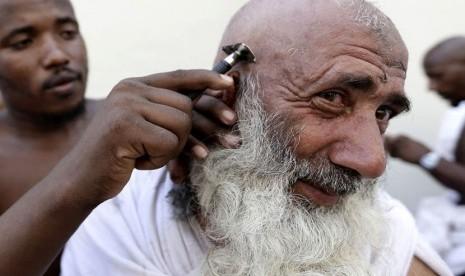 Seorang jamaah haji mencukur rambutnya usai melontar jumrah Aqabah di Mina, dekat kota suci Makkah, Jumat (26/10).    (Hassan Ammar/AP)