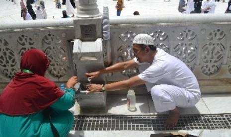 Seorang jamaah haji tengah mengambil air zamzam.