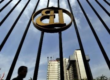 Seorang pejalan kaki melintasi logo Bank Indonesia di gedung BI kawasan Thamrin, Jakarta Pusat