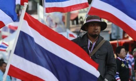 Seorang pengunjuk rasa anti-pemerintah berdiri di samping bendera nasional Thailand, saat berunjuk rasa di pusat kota Bangkok (15/1).   (Reuters/Chaiwat Subprasom)