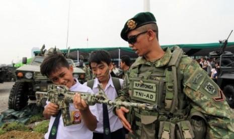 Seorang personil TNI AD menjelaskan peralatan persenjataan kepada sejumlah siswa pada sebuah pameran Alat Utama Sistem Persenjataan (Alutsista) TNI.