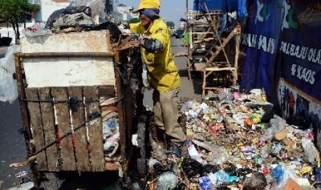 Seorang petugas kebersihan membersihkan sampah yang menumpuk di pinggir jalan (ilustrasi).