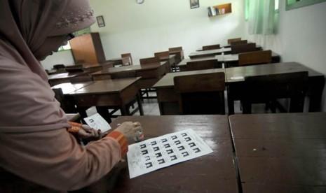 petugas sekolah menempelkan kartu peserta Ujian Nasional (UN) SMA