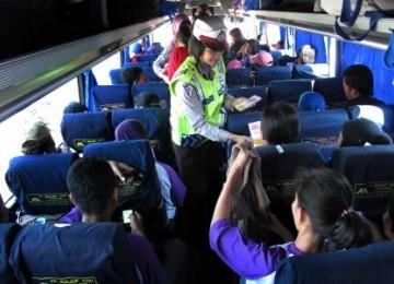 Seorang polwan anggota Sat Lantas Polrestabes Surabaya, membagikan brosur Sosialisasi Mudik Aman kepada penumpang bus di Terminal Purabaya Bungurasih Surabaya, Jatim, Jumat (26/8).