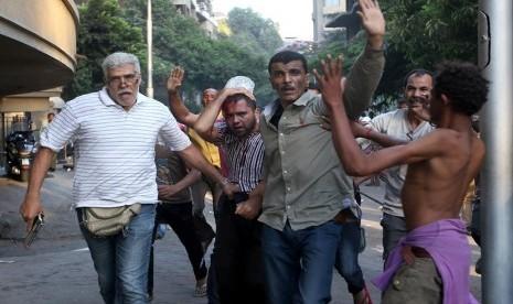 Seorang pria berpakaian sipil membawa senpi (kiri) menahan seorang pendukung Presiden Muhammad Mursi yang terluka dalam bentrokan yang terjadi di Kairo, Mesir, Senin (22/7).      (AP/ Hussein Malla)