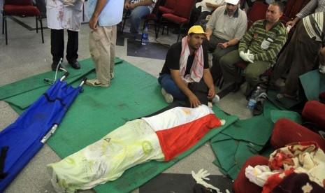 Seorang pria duduk disamping jenazah pendukung Mursi yang tewas terkena tembakan tentara di Kairo, Senin (8/7). (AP/Ahmed Gomaa)
