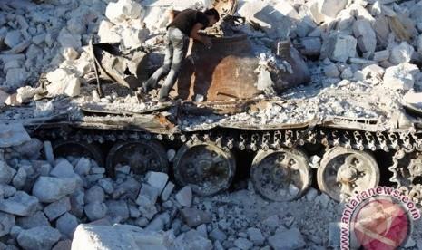 Seorang pria melihat tank Suriah yang hancur di Azaz, sekitar 47km dari Aleppo