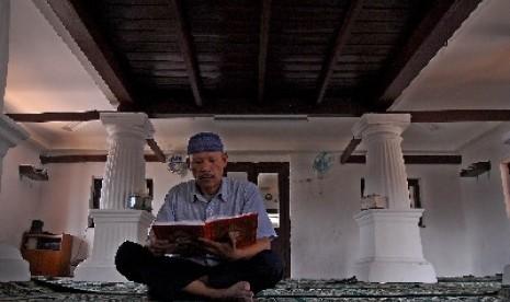 Seorang pria membaca Alquran usai shalat Dzuhur (ilustrasi).