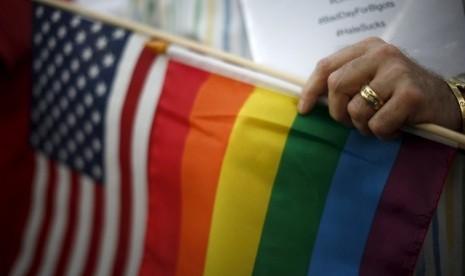 Seorang pria menggenggam bendera AS dan bendera pelangi, yang menjadi simbol kaum LGBT, menyusul keputusan dilegalkan perkawinan sejenis di seluruh AS.