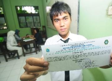 Seorang siswa menunjukkan hasil pengumuman kelulusan Ujian Nasional (UN) tingkat SMA/SMK/SMALB di SMK 10 Jakarta, Senin (16/5).