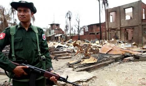 Seorang tentara Myanmar tengah berjaga di bangunan yang rusak di Sittwe, Rakhine, Myanmar.