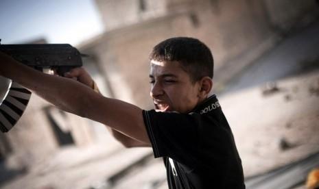 Seorang Tentara Pembebasan Suriah menembaki posisi tentara pemerintah Suriah di sebuah jalan di distrik Amariya Aleppo, Suriah, Senin (10/9).    (Manu Brabo/AP)