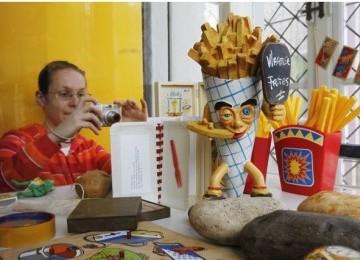 Seorang Turis mengabadikan melalui kameranya replika kentang goreng klasik.