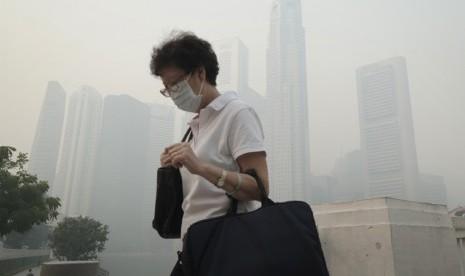 Seorang wanita memakai masker melintasi kawasan pusat bisnis di Singapura,Kamis (20/6).     (AP/Joseph Nair)
