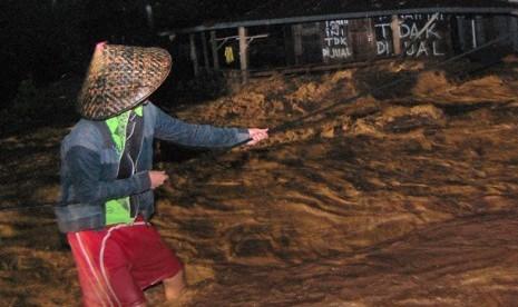 Seorang warga berpegangan pada sebuah tali saat banjir bandang, di Kelurahan Limaumanis, Kecamatan Pauh, Padang, Sumbar, Selasa (24/7) malam