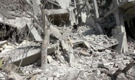 Seorang warga memeriksa bangunan yang hancur oleh serangan pasukan rezim Suriah di Arbeen, pinggiran kota Damsyik.