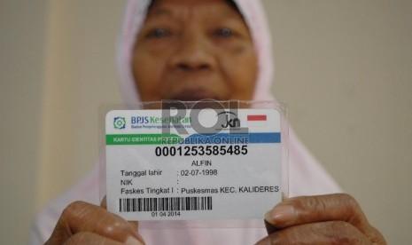 Seorang warga menunjukkan kartu BPJS Kesehatan miliknya.