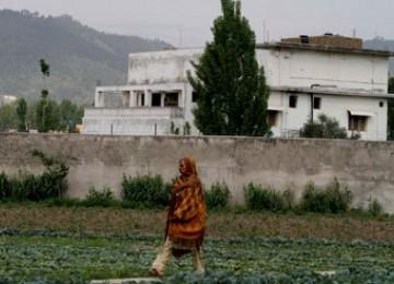 Seorang warga Pakistan melintas di depan bekas tempat tinggal pimpinan Al-Qaidah, Usamah bin Ladin, di Abbottabad, Pakistan.