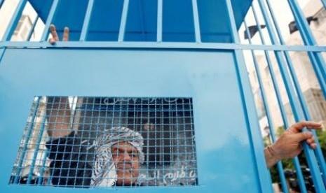 Seorang warga Palestina berdiri di belakang replika penjara, saat berunjuk rasa mendukung aksi mogok makan tahanan Palestina dalam penjara Israel.