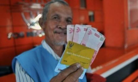 Seorang warga, Suyatno, 58 tahun, memperlihatkan Kartu Perlindungan Sosial (KPS) dan uang Bantuan Langsung Sementara Masyarakat (BLSM) sebesar Rp300 ribu untuk jangka dua bulan yang telah diambil di Kantor Pos Semarang, Jateng, Sabtu (22/6)