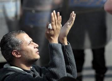Seorang pengunjuk rasa Mesir tampak berdoa di depan polisi yang bersiaga jelang unjuk rasa, Jumat (28/1)