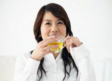 Seorang wanita tengah menikmati secangkir teh hijau.