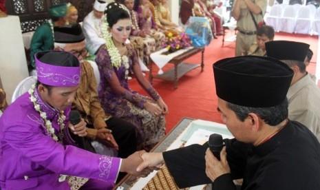 Sepasang pengantin melakukan ijab kabul pada pernikahan massal di rumah dinas Bupati Sleman, Senin (13/5). Pemkab Sleman mengakomodir pasangan - pasangan yang ingin menikah namun terkendala biaya