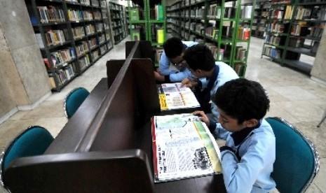 Siswa madrasah membaca buku di perpustakaan.