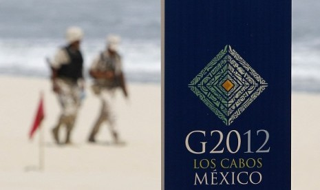 Soldiers walk near a sign of the G20 summit on a beach in Los Cabos June 17, 2012. G20 leaders will kick off two days of meetings in the Pacific resort of Los Cabos on Monday.