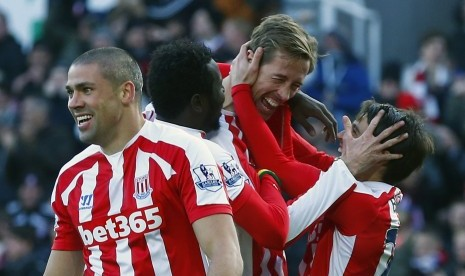 Peter Crouch (C) celebrates his goal against Arsenal with Bojan (R