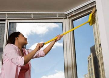Tampak seorang wanita membersihkan jendela menggunakan sapu. Namun, bersih berlebihan justru bisa memicu alergi.