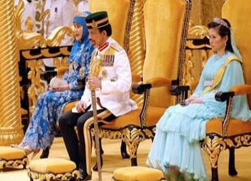 Tampak Sultan Hassanal Bolkiah didampingi oleh Ratu Saleha (kiri) dan istri keduanya, Azrinaz Mazhar Hakim pada perayaan ulangtahun Sultan ke-62.