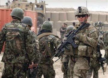 Tentara Afghanistan (kiri) berjalan melewati seorang tentara pasukan ISAF di Panjwai, Provinsi Kandahar, Afghanistan.