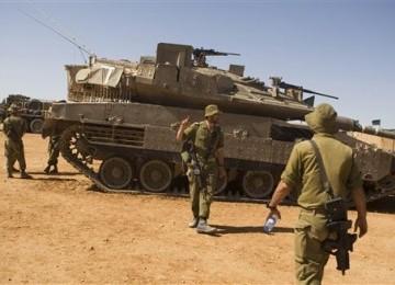 Tentara Israel berjalan dekat tank Merkava